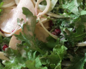 Close-up of greens, sliced pear and pomegranate