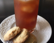 3 shortbread cookies and a glass of iced tea on a white plate