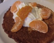 Oatmeal Pancakes topped with cream and mandarine orange slices.