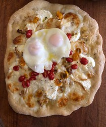 Dorothy's pizza with cherry tomatoes, fresh mozzarella, ricotta, leeks, fresh garlic, topped with 2 fried eggs.