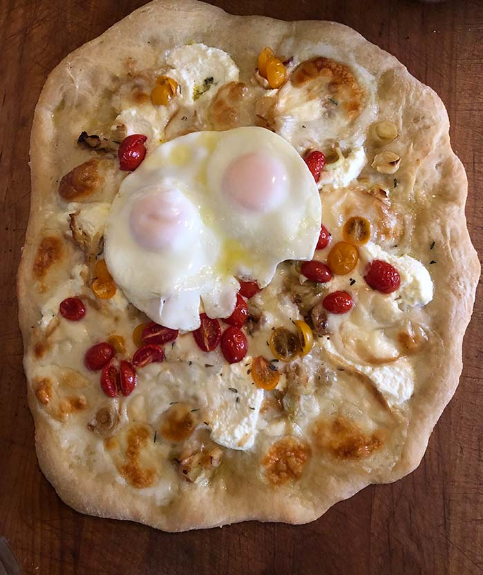 Dorothy's pizza with cherry tomatoes, fresh mozzarella and ricotta baked and topped with 2 fried eggs.