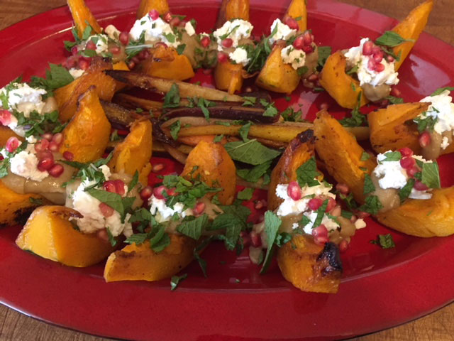 roasted kabosha squash topped with mint and pomegranate on a red platter.