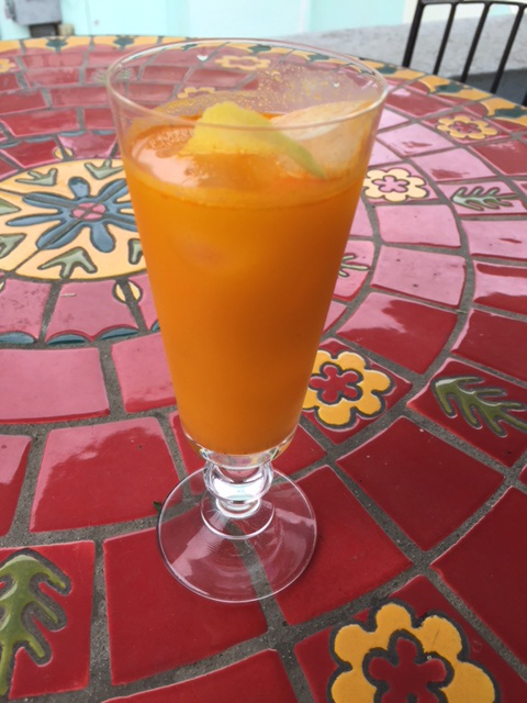 glass of turmeric tonic on a colorful table